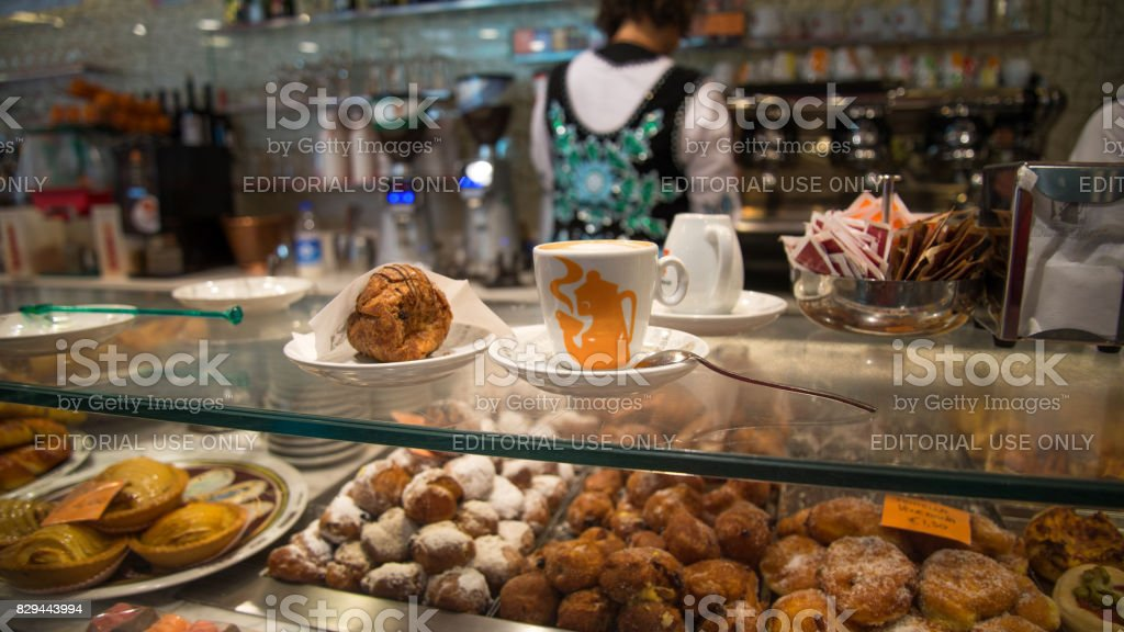 Cup of coffee with croissant inside a coffee shop stock photo