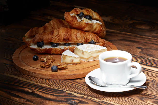 Taza de café con croissants, queso Camembert y arándanos sobre un fondo de madera. - foto de stock