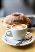 istock Cup of coffee with croissants on the table 897362454