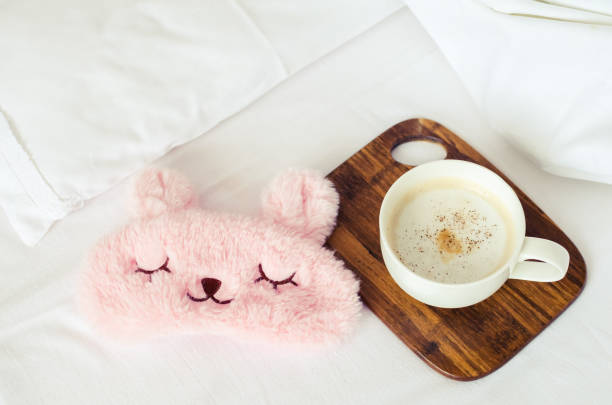 Cup of coffee with cute pink sleep mask stock photo