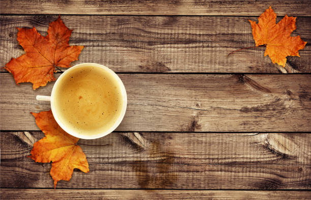 Cup of coffee with dry autumn leaves on wood stock photo