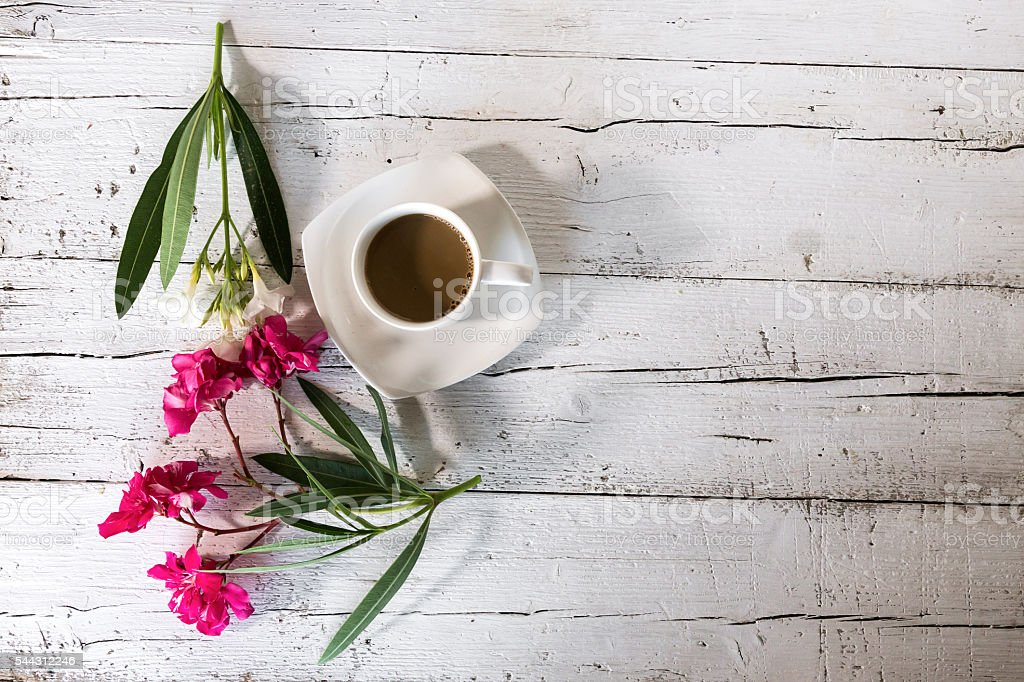 Cup of latte with bouquet flowers on old wooden table