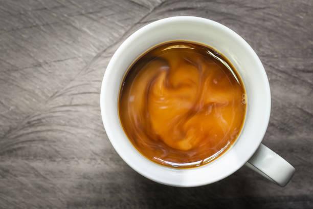 filiżanka kawy z płynącym mlekiem na drewnianym tle, strzał nad głową. - coffee zdjęcia i obrazy z banku zdjęć