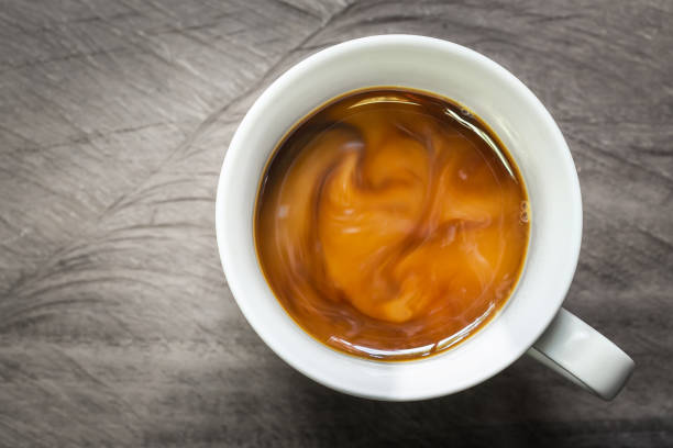 cup of coffee with flowing milk on wooden background, overhead shot. - caffè foto e immagini stock