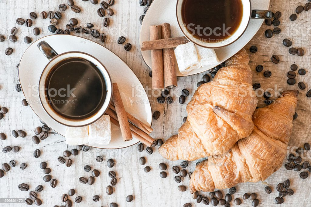 Cup of coffee with grains, croissant on wooden background royalty-free stock photo