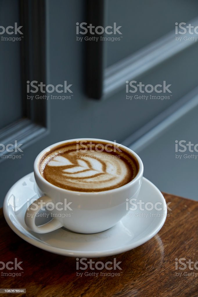 A cup of coffee with heart pattern in a white cup on rustic wooden...