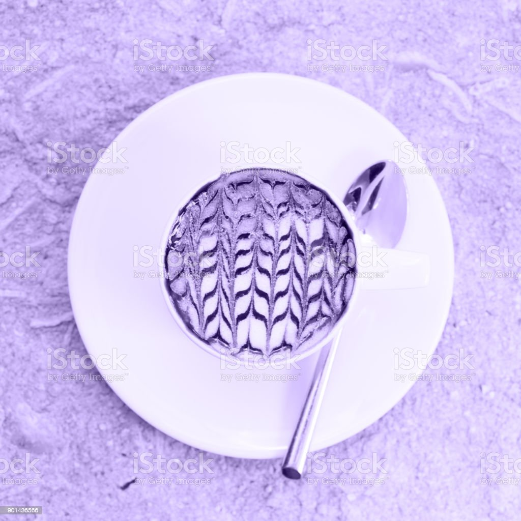 A cup of coffee with latte art. Ultra violet tone, color of the year 2018 stock photo