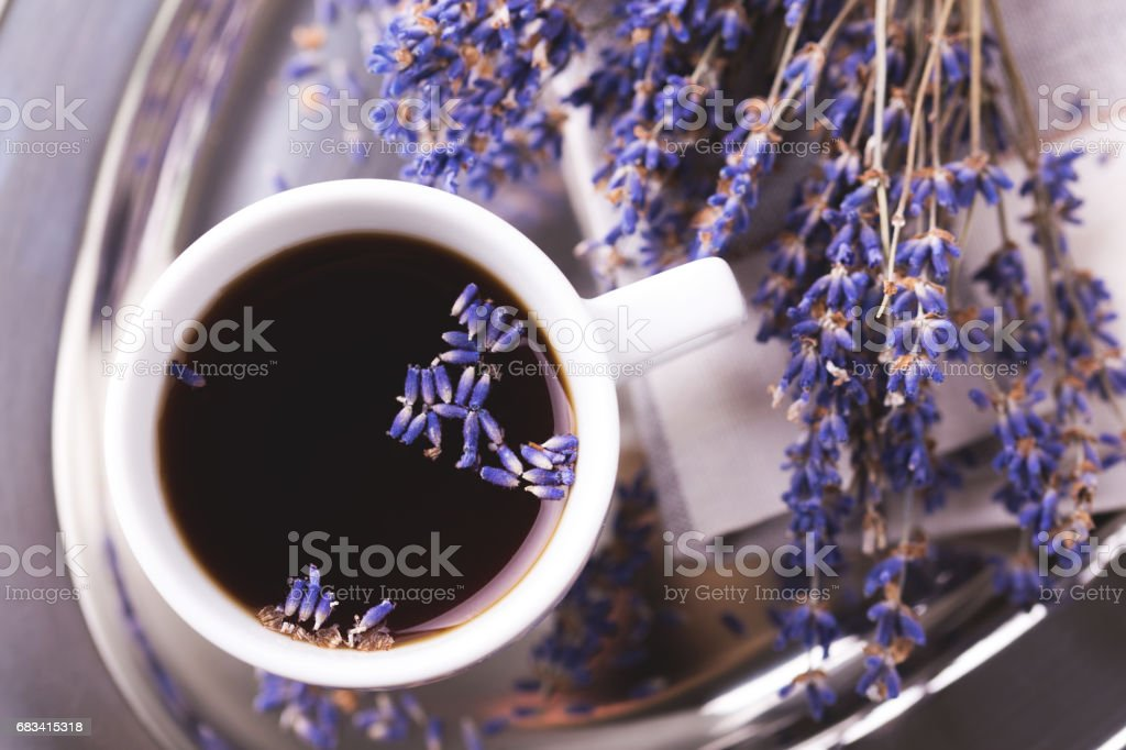 Cup of coffee with lavender flowers on dark stone table. Lifestyle...