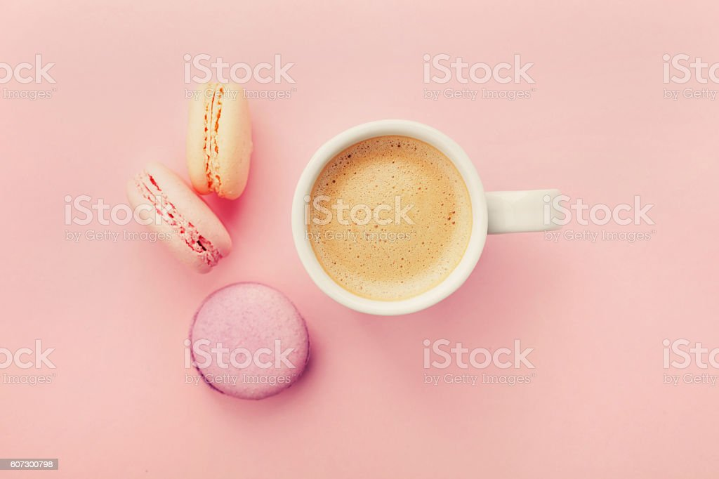 Cup of coffee with macaron on pink background from above