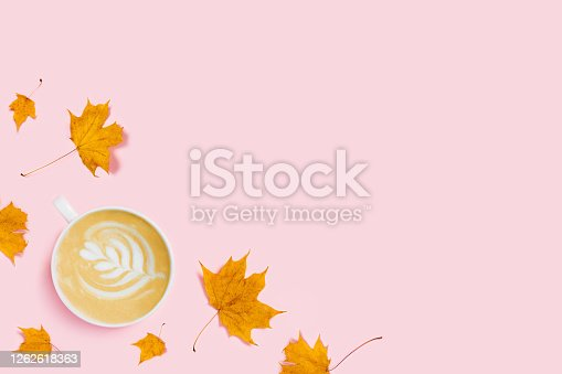 Autumn composition in pastel colors. Pink background with cup of cappuccino surrounded by maple leaves. Flat lay, top view, copy space.