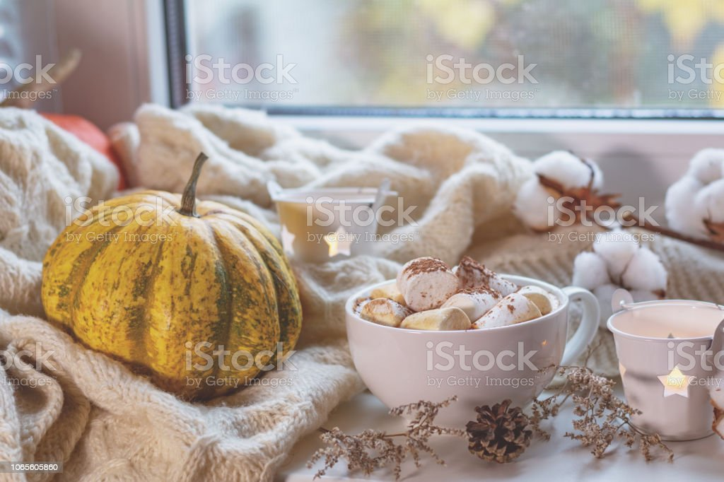 Cup of coffee with marshmallow on windowsill, cozy home concept stock photo