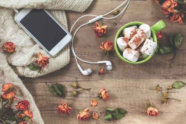 Cup of coffee with marshmallow, white knitting wool, dried roses flowers, mobile phone and headphones stock photo