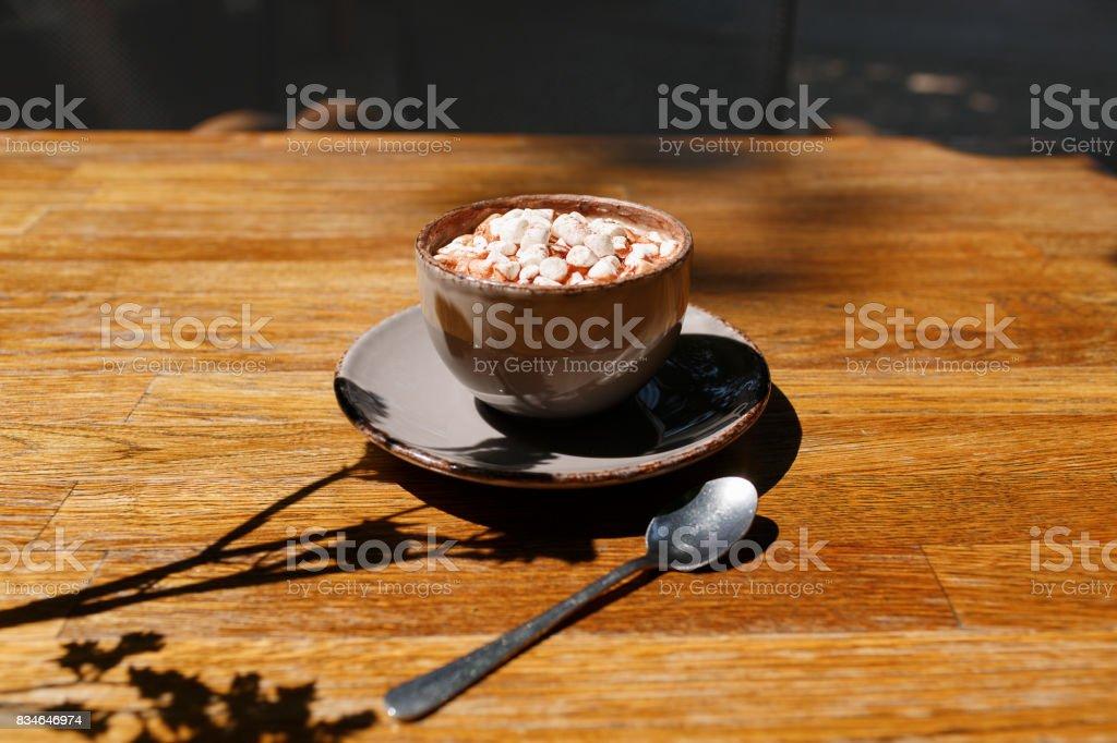 A close-up of a gray porcelain mug of sugar cappuccino with...