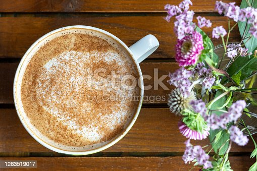 A cup of coffee with milk and beautiful lilac-hued flowers, view from above