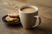 Cup of coffee with milk and cookies with chocolate pieces on the brown wooden table. Resting and enjoying time with coffee and sweets. Drink and snack concept.