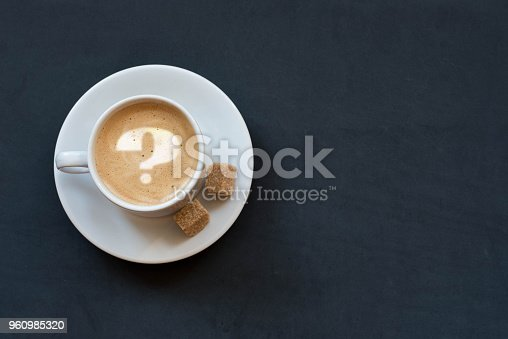 istock Cup of coffee with milk, cane sugar and question mark on dark background. Top view. Copy space 960985320