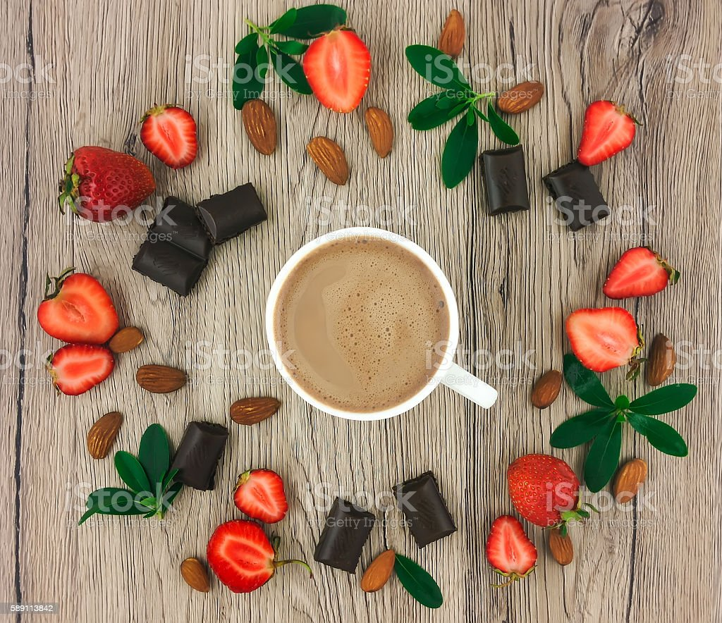 Cup of coffee with milk, chocolate and strawberries. Flat lay