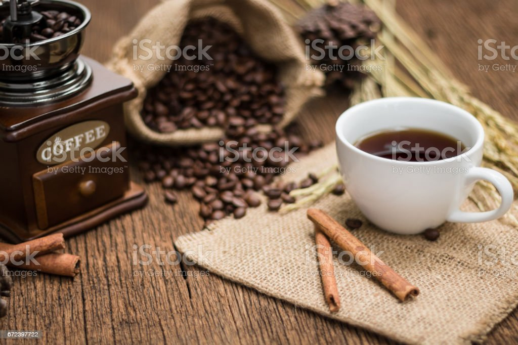 A cup of coffee with old vintage coffee grinder and roasted coffee beans. stock photo