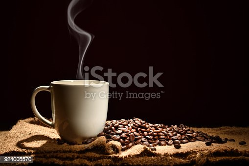 istock Cup of coffee with smoke and coffee beans on black background 924005570