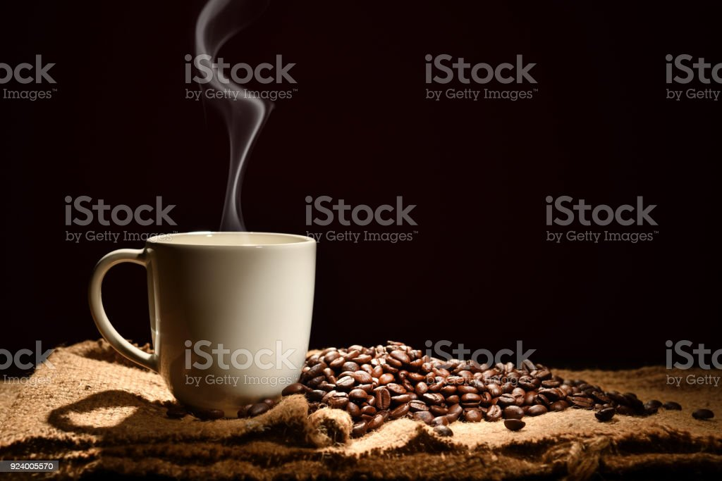 Cup of coffee with smoke and coffee beans on black background stock photo