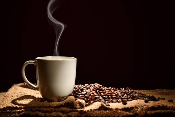 cup of coffee with smoke and coffee beans on black background - coffee stock pictures, royalty-free photos & images
