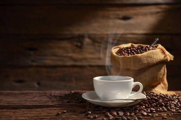 filiżanka kawy z dymem i ziaren kawy na starym drewnianym tle - coffee zdjęcia i obrazy z banku zdjęć
