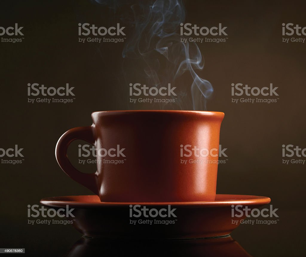 Cup of coffee with smoke over dark background stock photo