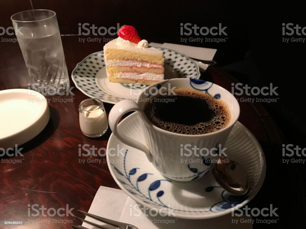 Cup of coffee with strawberries cake lying on the wooden table stock photo