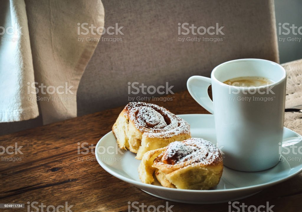 Cup of coffee with two cinnamon buns on white plate standing on...