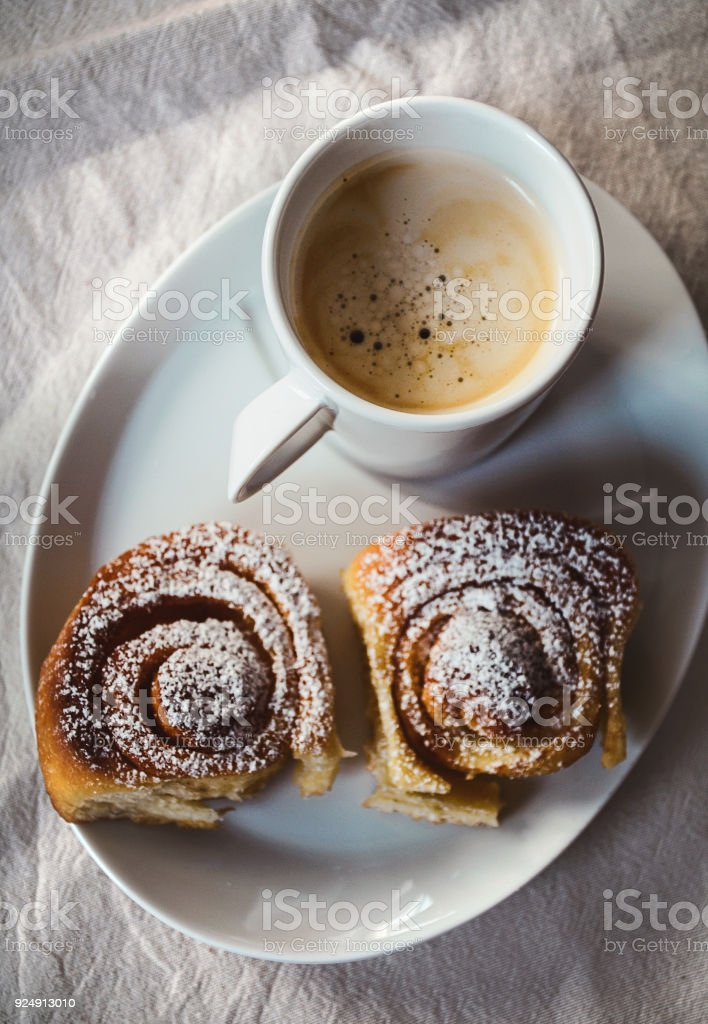 Cup of coffee with two cinnamon buns on white plate. View from above,...