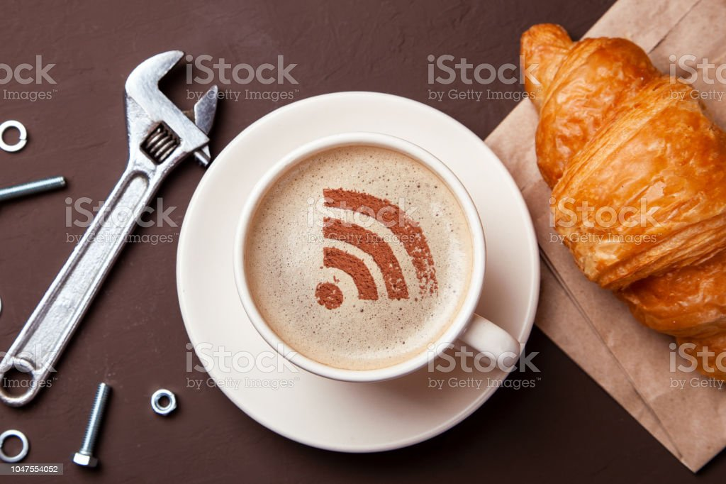 Cup of coffee with WiFi sign on the foam. Free access point to the Internet WiFi. I like coffee break with croissant. Repair service concept. Technical support, wrench stock photo