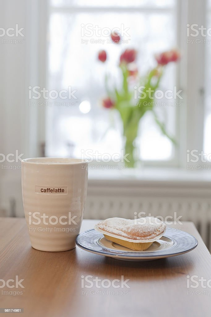 cup of coffelatte and a heartshaped bun royalty-free stock photo