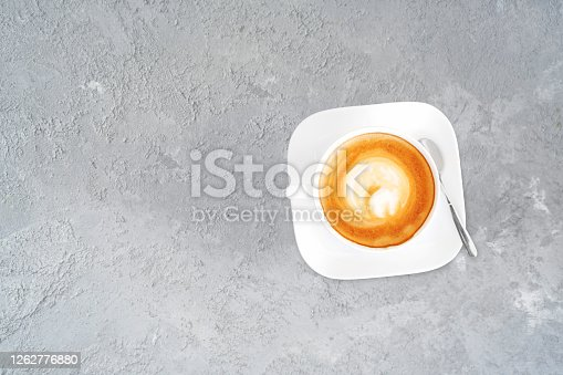 Cup of creamy coffee on the stone background. Copy space.