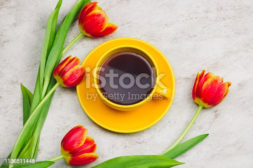 cup of drink  and tulips on marble table, top view