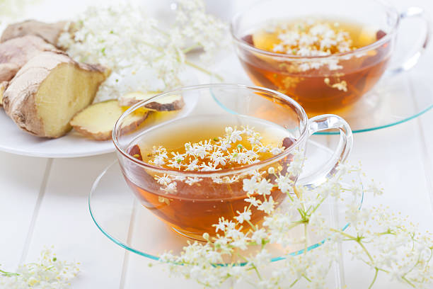 Cup of elder flower tea with ginger stock photo