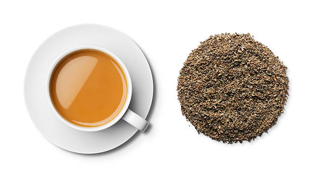 cup of english breakfast tea and leaves overhead - tea leaf stock photos and pictures