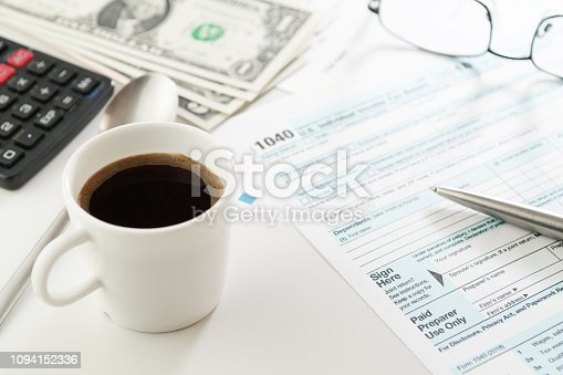 istock Cup of espresso and income tax return form with money, calculator and glasses 1094152336