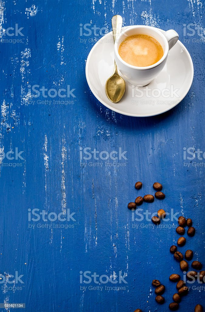 Cup of espresso coffee and beans on wooden blue painted stock photo