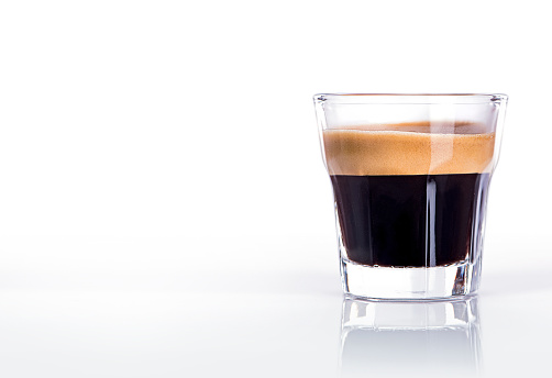 Close up of a glass of espresso on a black background