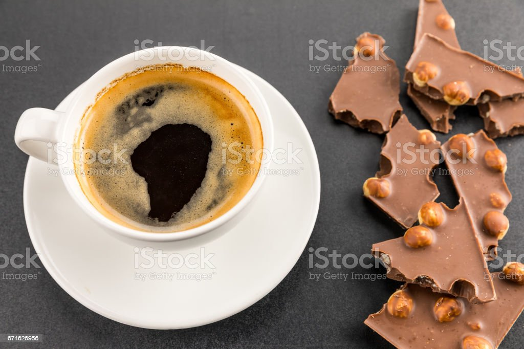 cup of espresso coffee with chocolate with nuts on black