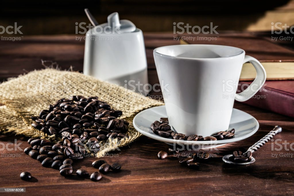 Cup of Espresso coffee with roasted raw coffee beans. Natural lighting stock photo