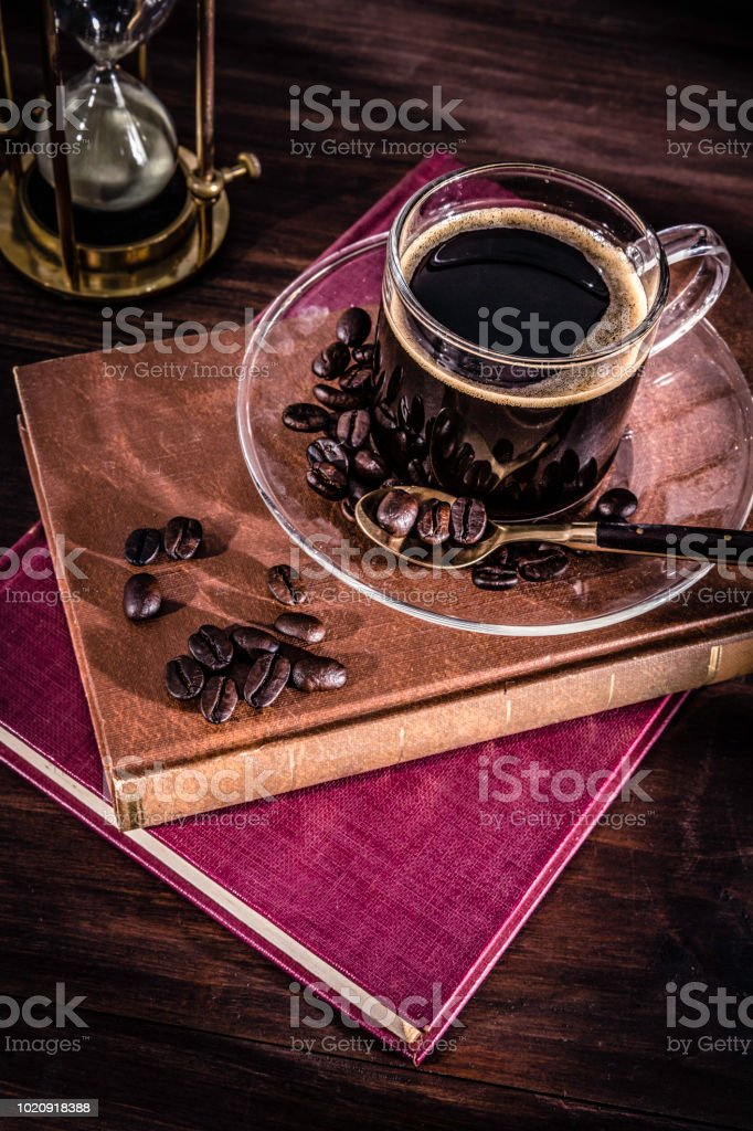 Cup of Espresso coffee with roasted raw coffee beans. Natural lighting with books and hourglass stock photo