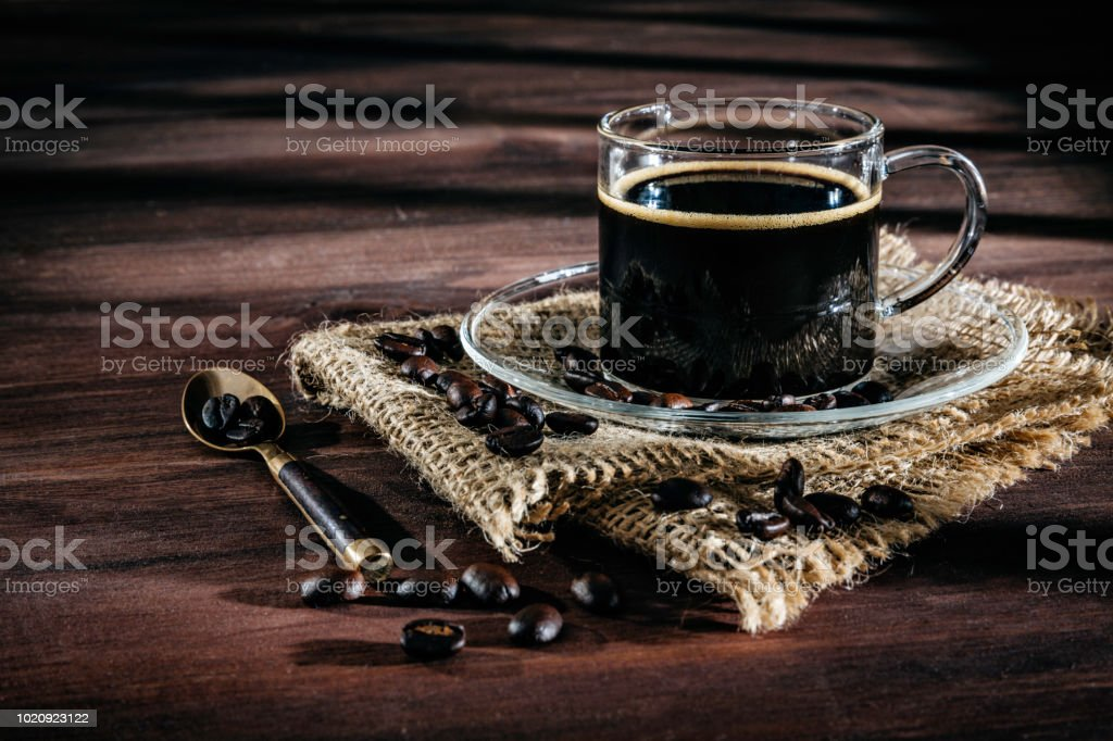 Cup of Espresso coffee with roasted raw coffee beans. Natural lighting in a rustic kitchen stock photo