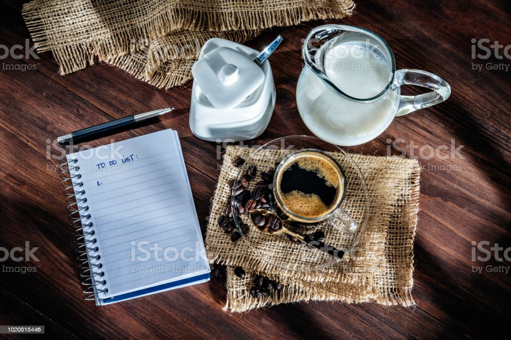Cup of Espresso coffee with roasted raw coffee beans. To do list in notebook. stock photo