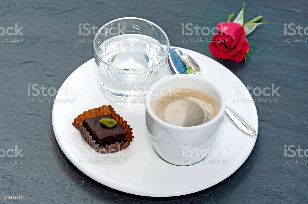 Cup of espresso, glass of water and chocolate stock photo