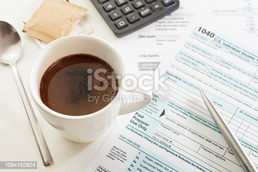 istock Cup of espresso on white table with income tax return form, pen and calculator 1094152624