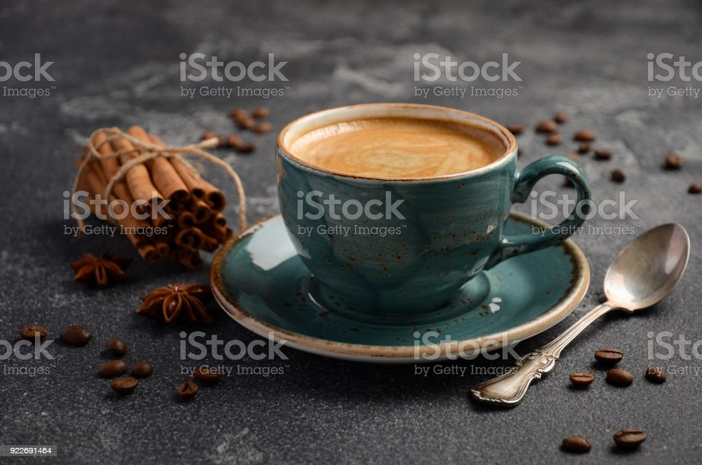 Cup of fresh coffee with Amaretti cookies on a black concrete or stone background stock photo