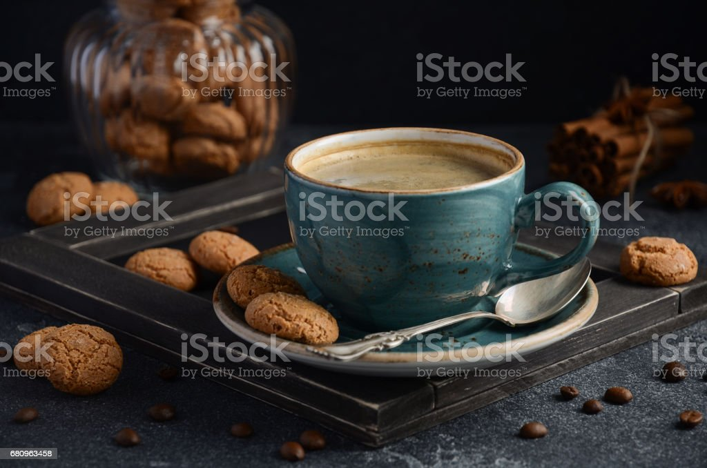 Cup of fresh coffee with Amaretti cookies on dark background stock photo