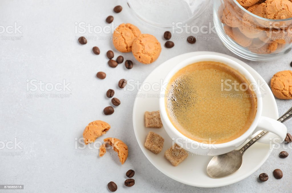 Cup of fresh coffee with Amaretti cookies on gray concrete or stone background stock photo