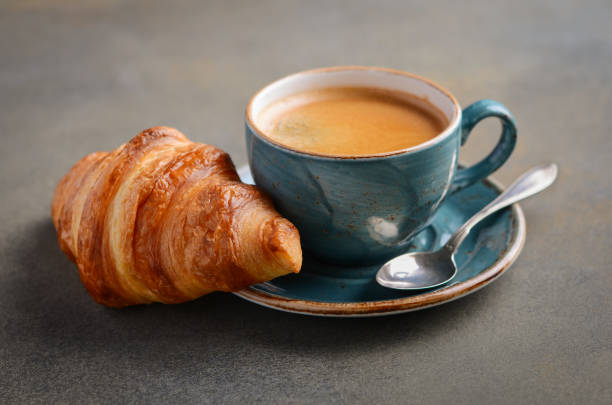 Cup of fresh coffee with croissant on concrete background. Cup of fresh coffee with croissant on concrete background, selective focus. croissant stock pictures, royalty-free photos & images